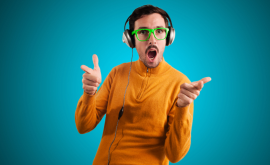 Education and modern technologies. The concept of audio books. A bald man in glasses with closed eyes and a smile, listening to the reading of a book through headphones. Yellow background. Close up.
