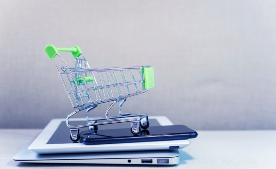 Online business and e-commerce or shopping online concept. Shopping basket on top of stack of laptop, tablet and mobile phone. Wireless technology for business with free copy space.