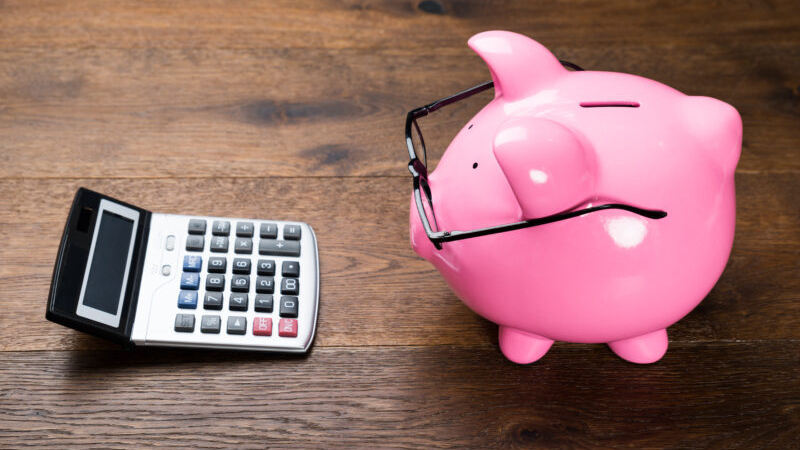 Piggybank With Eyeglasses And Calculator On Wooden Table